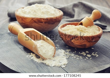 Raw rice and flour in bowls with scoop on wooden background