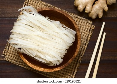 Raw rice flour noodles in wooden bowl, photographed overhead on dark wood with natural light (Selective Focus, Focus on the top of the noodles)