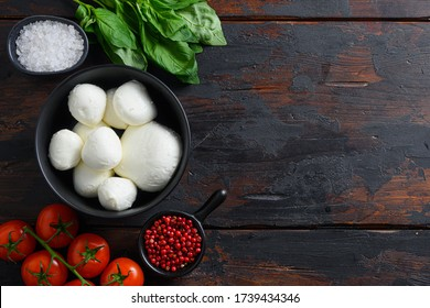 Raw ripe Mozzarella cheese balls with fresh basil leaves and cherry tomatoes, the ingredients , on old wood background top view space for text