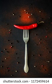Raw ripe red chili pepper on fork with pepper peas and powder lying on dark wooden background. Top view. Flat lay