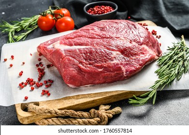 Raw Round beef cut on a cutting board. Black background. Top view