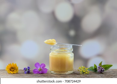 Raw royal bee jelly on the table surrounded by flower on a gray background with clear bubbles
