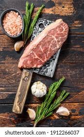 Raw rump cap steak on a meat cleaver. Dark wooden background. Top view