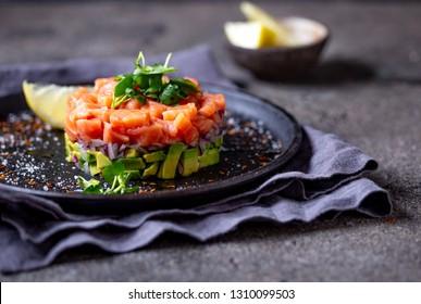Raw Lachs, Avocado violetter Zwiebelsalat serviert in kulinarischem Ring auf schwarzem Teller. schwarzer Betonhintergrund