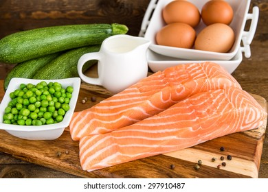 Raw salmon filet with vegetables on wooden cutting board. Ingredients for clafoutis