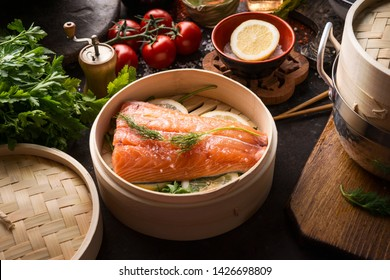 Raw salmon fillet in bamboo steamer on dark rustic kitchen table with ingredients and tools. Healthy eating and cooking. Dieting concept. Asian cuisine