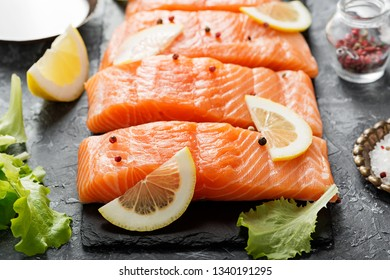 Raw salmon fillet and ingredients for cooking on a dark background.