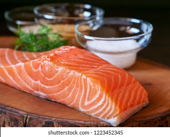 Raw salmon fillet and ingredients for making gravlax. Salt, sugar and dill in bowls in the background for dry cure marinade, dark background.