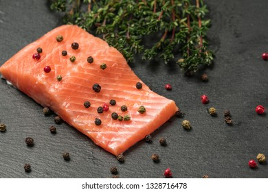 34ee98e83d81 Raw salmon fillet on a dark slate background. Trout fillet with thyme and  peppercorns.