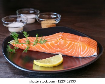 Raw salmon fillet on lack plate and ingredients for making gravlax. Salt, sugar and dill in bowls in the background for dry cure marinade, dark background.