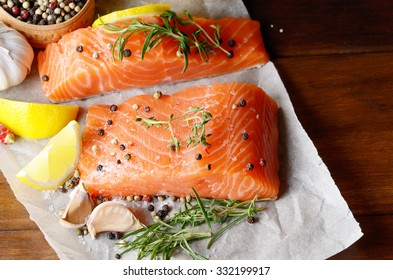 Raw salmon fillet with rosemary pepper sweetbread and salt on baking paper rustic theme with copy-space