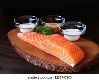 Raw salmon fillet, Salt, sugar in bowls, dill, ingredients for dry cure marinade on dark background. Homemade gravlax preparation.