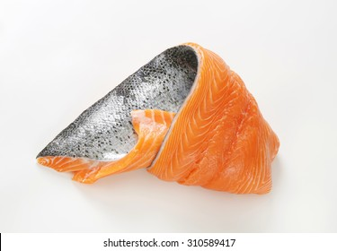 raw salmon fillet with silver skin on white background