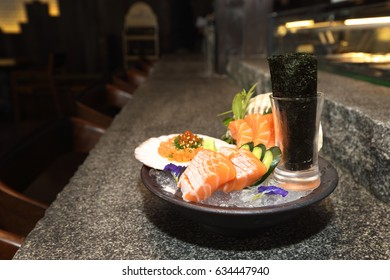 Raw salmon fillet slicing fresh fishes for sashimi, Japanese Cousin in Fine stone table with shell and sea weed decorated