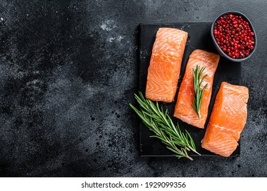 Raw salmon fillet steaks on marble board with herbs. Black background. Top view. Copy space.