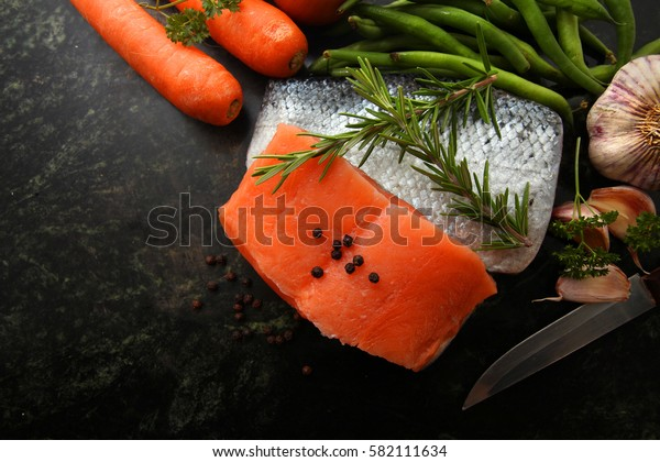 raw salmon fillets with other raw ingredients over marble stone chopping board background