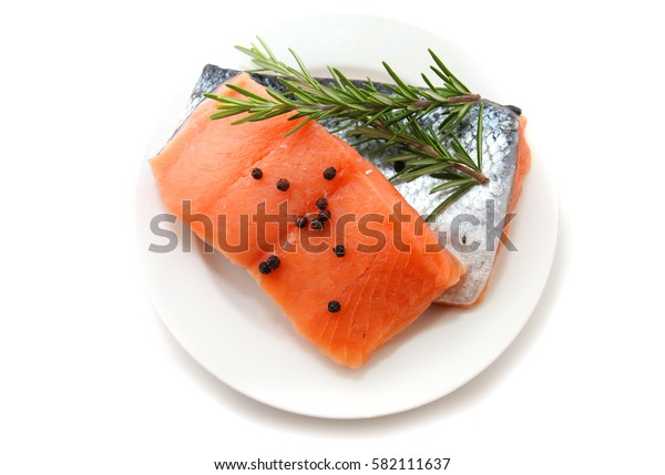 raw salmon fillets with other raw ingredients isolated on white background