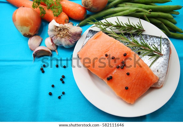 raw salmon fillets with other raw ingredients over blue table cloth background