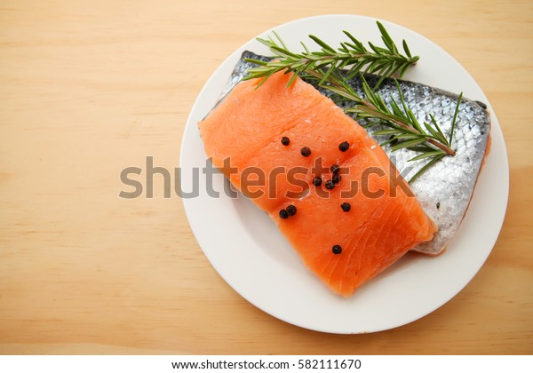 raw salmon fillets with other raw ingredients over wooden table background