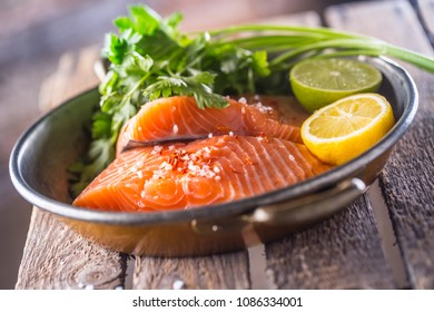 Raw salmon fillets with parsley herbs lime lemon salt and dried saffron.