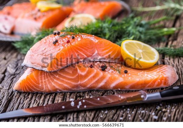 生鮭魚片胡椒鹽蒔蘿檸檬和迷迭香木桌上。