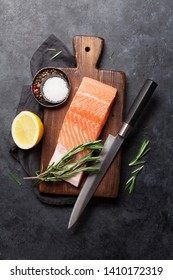 Raw salmon fish fillet and ingredients for cooking on stone table. Top view flat lay