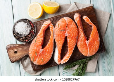 Raw salmon fish fillet with spices cooking on cutting board. Top view