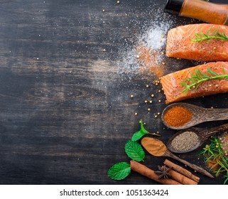 Raw salmon fish fillet with spoon herbs and spices on rustic wooden background,top view