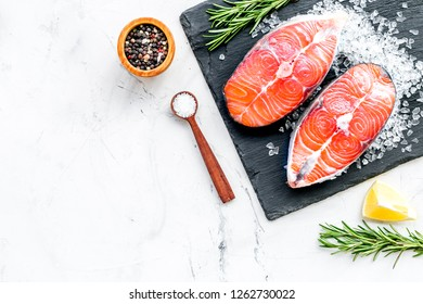 Raw salmon fish on black plates for cooking steaks on marble restaurant kitchen background top view space for text