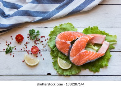 Raw salmon fish steak with lemon and spices, ready to cook, on white background