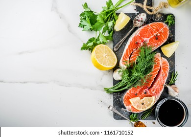 Raw salmon fish steaks with lemon, herbs, olive oil, ready for grill, slate cutting board, white marble background copy space above