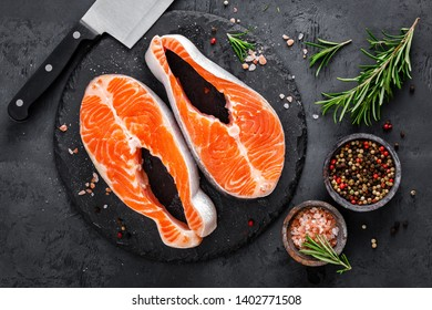 Raw salmon fish steaks on black background
