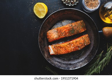 Raw salmon pieces with spices and dill on pan. View from above.