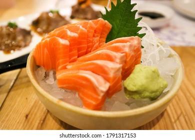 Raw Salmon sashimi on ice and bowl