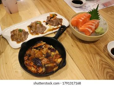 Raw Salmon sashimi on ice and bowl and wood desk