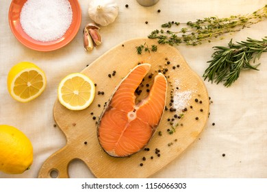 Raw salmon steak on a light wooden background
