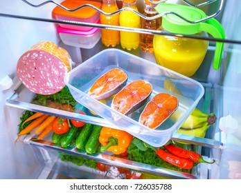 Raw Salmon steak in the open refrigerator