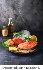Raw salmon steak and a piece of fresh fish on an iron dish. Ingredients for cooking - lemon, garlic, salt, pepper, oil. Healthy food