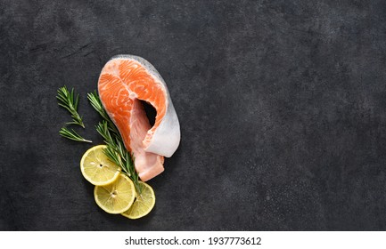 Raw salmon steak, salt and rosemary on a concrete black background. Ingredients for cooking fish.