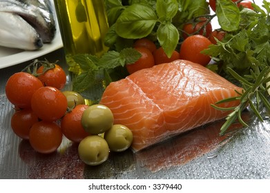 raw salmon steak with vegetables and olive oil in background