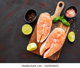 Raw salmon steaks and ingredients on a black slate board
