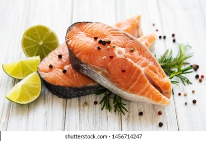 Raw salmon steaks and ingredients on a old wooden table