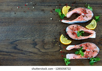 Raw salmon steaks on wooden table