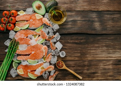 Raw salmon steaks and shrimps with ice, lemon and lime, seasonings, garlic, olive oil, cherry tomatoes, avocado and asparagus on a wooden background. Top view, copy space