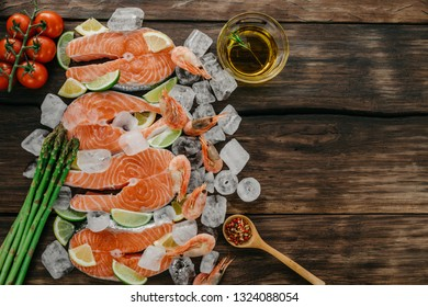 Raw salmon steaks and shrimps with ice, lemon and lime, seasonings, garlic, olive oil, cherry tomatoes and asparagus on a wooden background. Top view, copy space