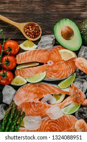 Raw salmon steaks and shrimps with ice, lemon and lime, seasonings, garlic, olive oil, cherry tomatoes, avocado and asparagus on a wooden background. Top view, closeup