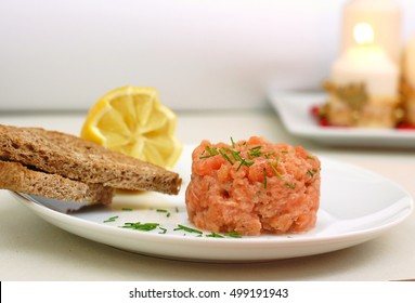 Raw salmon tartar with roasted bread and lemon, front horizontal view