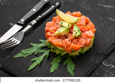 Raw salmon tartare. Fresh salmon, avocado and arugula salad in a culinary ring on a slate plate, black stone background. Selective focus