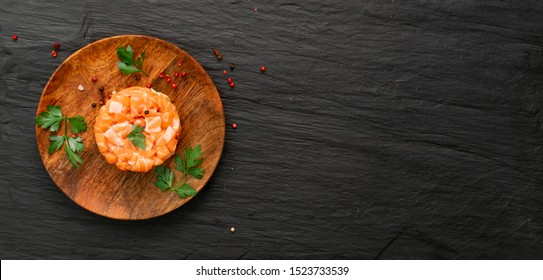 Raw salmon tartare, trout tartar or red fish cubes salad with fresh avocado on black stone background. Delicious raw tuna tatar or sashimi on wooden rustic restaurant plate with copyspace top view