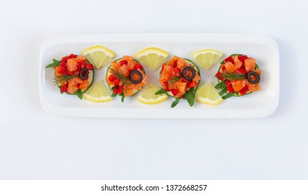 Raw salted salmon with rucola, red pepper, lemon and zucchini on a white plate,white background.